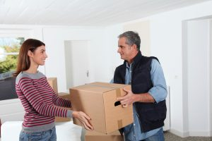 Young woman with removal man holding boxes